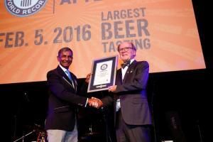 """Prav Patel, a Guinness Világrekordok hivatalos döntőbírója átadja Dr. Pearse Lyons-nak, az Alltech alapítójának és elnökének a hivatalos oklevelet, amellyel az Alltech Craft Brews and Food Fair ünnepséget tüntette ki """"a világ legnagyobb sörkóstolása"""" új rekordjának felállításáért. A most már negyedik éve megrendezett fesztivál az idei évben több mint 10 000 látogatót vonzott február elején."""